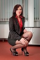 Junge Sekretärin in der Hockestellung am Boden