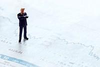 Figur eines Geschäftsmannes steht auf dem Finanzteil einer Zeitung mit einer Aktienkurve