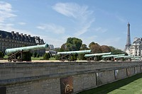 North moat of the Hôtel des Invalides with historical cannons taken to the enemy, and tour Eiffel in the background, Paris, France.