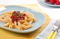 Nudeln mit Tomatensauce und frischem Schnittlauch auf blauem Ges