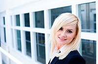 Attractive young blonde woman standing in front of a white framed window facade which gives the image strong architectural perspective