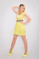 Junge hübsche Frau im elegenten zitronengelben Minikleid mit gelben Pumps