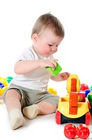 The little boy plays multi_coloured toys isolated