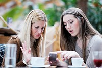 very cute smiling women drinking a coffee sitting inside in cafe restaurant