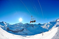 Ski lift _ happy skiers use vertical transport on ski vacation at sunny winter snow day