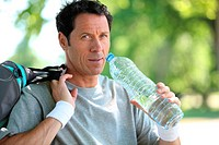 man in sports clothes drinking water