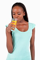 Young woman looking into her glass of orange juice
