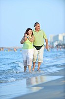happy senior mature elderly people couple have romantic time on beach at sunset