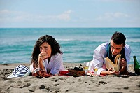 happy young couple enjoying picnic on the beach and have good time on summer vacations