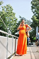BEAUTIFUL YOUNG PREGNANT WOMAN WALKING OUTDOOR AND TAKING ON CELLPHONE