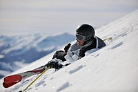 young skier relaxing in snow and looking mountain range at beautiful sunny winter day