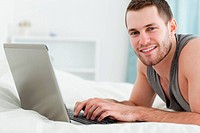 Happy man using a laptop while lying on his belly