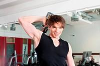 Sport _ Mann trainiert mit Hanteln im Fitnessstudio