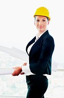 young architect woman in business suit portrait with yellow hemet and blueprints