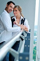 romantic happy couple relax and have fun at balcony in their new home apartment