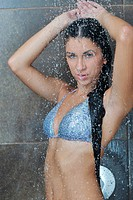 Portrait of a sexy young woman enjoing bath under water shower