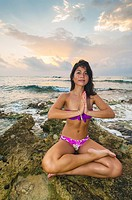 A woman at sunrise doing yoga along the Caribbean Sea at Akumal, Riviera Maya, Mexico