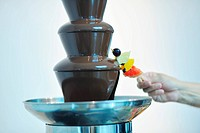 liquid chocolate fountain closeup and fresh fruits on stick hold by hand at wedding party event