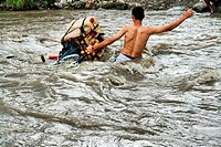 A Colombian gasoline smuggler with his bicycle fighting the wild waves of the river Táchira on the Colombian-Venezuelan border, 3 May 2006  The way th...