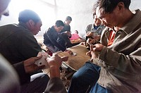 Labor workers playing a friendly game of cards at the San Huang Zhai Monastery on Song Mountain, China