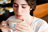 Woman blowing on coffee in cafe