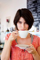 Smiling woman drinking coffee in cafe