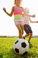 Girls playing soccer in field
