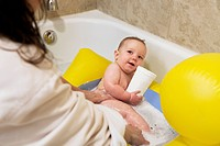 Caucasian mother bathing baby boy