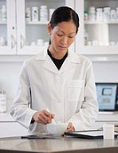 Asian pharmacist preparing medication