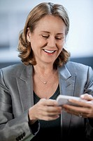Caucasian businesswoman text messaging on cell phone