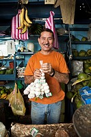 Hispanic man holding garlic in shop