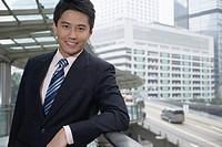 Smiling businessman leaning on banister