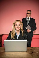 Germany, Stuttgart, Businessman and woman with laptop, smiling, portrait