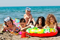 happy child group have fun on beach while playing with toys running jumping