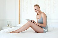 Woman sitting on a bed using a digital tablet