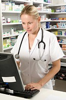 Pharmacist working at a computer in a pharmacy