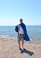 funny superhero standin at beach on hot sand