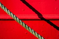 Detail of red tugboat with rope