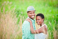 Young couple standing in long grass in park, Johannesburg, South Africa