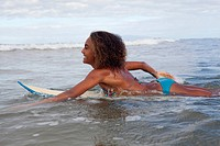 Surfer girl paddles out on her surfboard