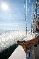 Woman Sitting on Edge of Boat on Ocean