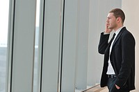 young business man talk by cellphone over bright window in big hall