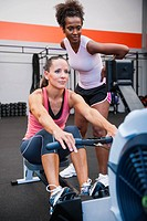 Woman exercising on row machine supervised by her trainer