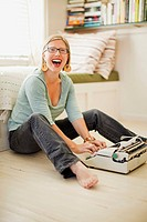 Woman laughs as she types on her white, antique typewriter that sits on the floor in front of her. Woman is looking at the camera and opening her mout...