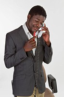 Young black man in a suit making a phone call in an office, looking pensively