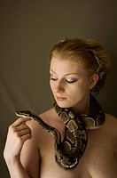 Woman playing with snake around her neck