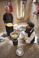 Afghan refugees preparing a potatoe meal, Afghanistan