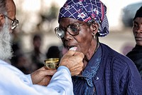Older woman taking communion from priest in Chalucuane, Mozambique
