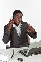 Young dark-skinned man sitting at a laptop and holding a phone, smiling while making a thumbs-up gesture