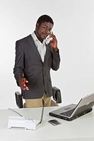 Young dark-skinned man holding a phone in an office